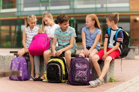 primary education, friendship, childhood, communication and people concept - group of happy elementary school students with backpacks sitting on bench and talking outdoors Stok Fotoğraf