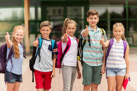 primary education, friendship, childhood, gesture and people concept - group of happy elementary school students with backpacks showing thumbs up outdoors Reklamní fotografie - 64214058