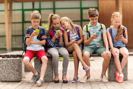 primary education, friendship, childhood, technology and people concept - group of happy elementary school students with smartphones and backpacks sitting on bench outdoors Stok Fotoğraf