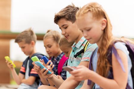 primair onderwijs, vriendschap, jeugd, technologie en mensen concept - groep van gelukkige basisschoolleerlingen met smartphones en rugzakken zittend op bankje buiten