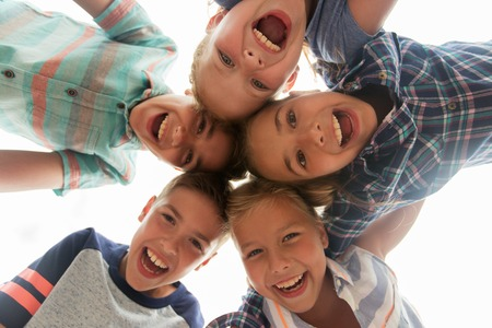 kids outside: childhood, leisure, friendship and people concept - group of smiling happy laughing children faces in circle