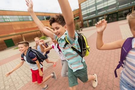 niño escuela: la educación primaria y el concepto de personas - grupo de estudiantes de la escuela primaria felices con mochilas corriendo y agitando las manos al aire libre (fuera de foco, movimiento de la imagen borrosa) Foto de archivo