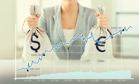 american banker: business, finance, saving, banking and people concept - close up of woman hands holding dollar and euro money bags with growing chart Stock Photo