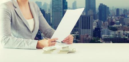 salarios: negocios, finanzas, impuestos y concepto de la gente - cerca de la mujer de las manos con nosotros y dinero informe fiscal formulario de papel del dólar sobre el fondo de la ciudad Foto de archivo