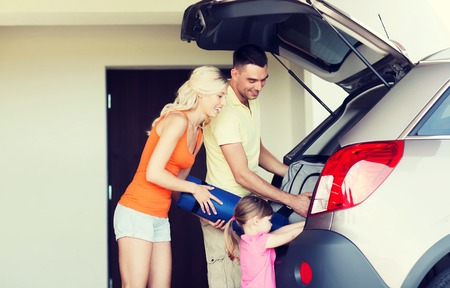 car trunk: transport, leisure, travel, road trip and people concept - happy family packing things into car at home parking