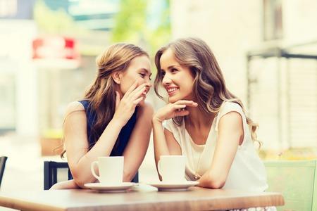 concepto de la gente, la comunicación y la amistad - sonrientes mujeres jóvenes bebiendo café o té y chismeando en el café al aire libre Foto de archivo