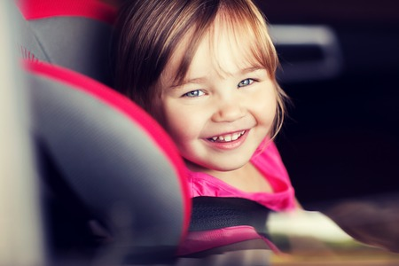 transport, safety, childhood road trip and people concept - happy little girl sitting in baby car seat