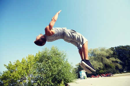BACKFLIP: fitness, sport, parkour and people concept - young man jumping in summer park Stock Photo