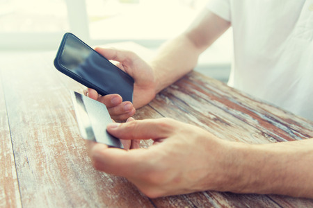 emoney: business, technology, cash free and internet people concept - close up of male hands holding smart phone and credit card on wooden table