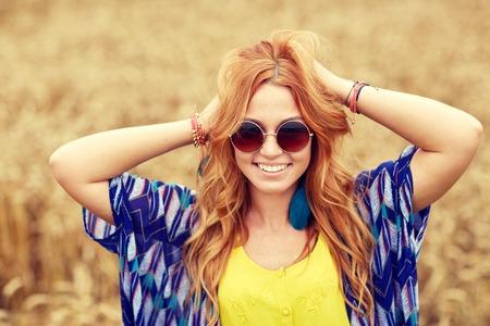 mujer hippie: naturaleza, verano, la cultura juvenil y la gente concepto - joven hippie pelirroja sonriente en gafas de sol al aire libre