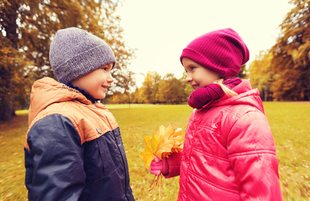 two children: childhood, leisure, friendship and people concept - happy little boy giving maple leaves to girl in autumn park