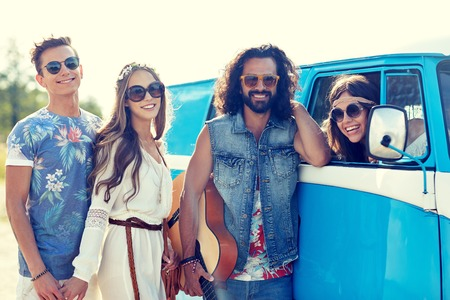 trip over: summer holidays, road trip, vacation, travel and people concept - smiling young hippie friends with guitar over minivan car