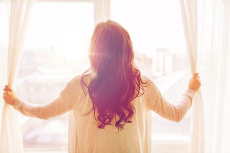 Lidé a naděje koncepce - zblízka šťastné ženy otevírání oken záclony Reklamní fotografie