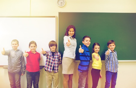 thumbs up group: education, elementary, gesture and people concept - group of school kids and teacher showing thumbs up in classroom