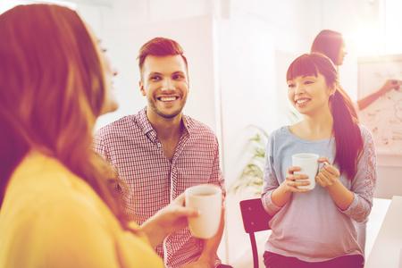 bedrijfsleven, opstarten en mensen concept - gelukkig creatieve team of studenten drinken koffie en praten op het kantoor van