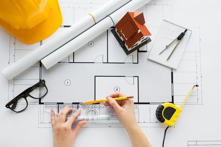 concepto de negocio, arquitectura, construcción, construcción y personas: cerca de las manos del arquitecto con una regla y un lápiz que miden el plano de la casa viviente