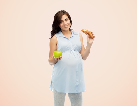 pregnancy, healthy eating, junk food and people concept - happy pregnant woman choosing between green apple and croissant over beige background