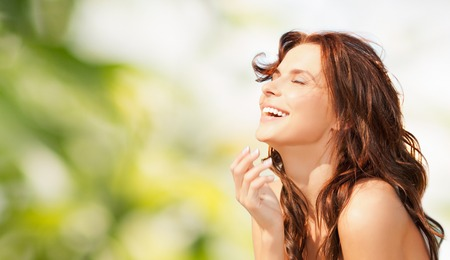 beauty, summer, emotion, expression and people concept - happy beautiful woman over green natural background