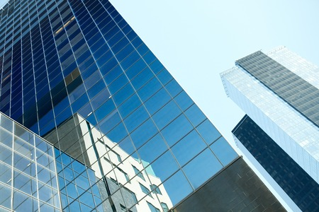 architecture, exterior, business, real estate and construction concept - close up of office building or skyscraper and sky