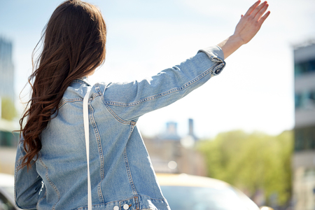 catching taxi: gesture, hitch-hike, travel, tourism and people concept - young woman or teenage girl catching taxi on city street or hitch-hiking Stock Photo