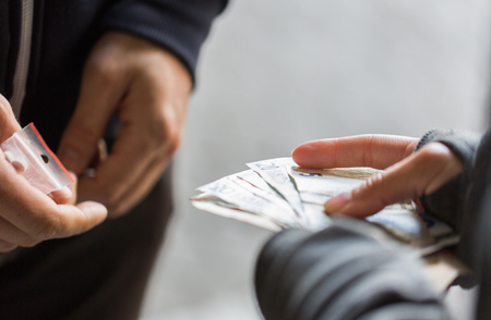 drug trafficking: drug trafficking, crime, addiction and sale concept - close up of addict with money buying dose from dealer on street