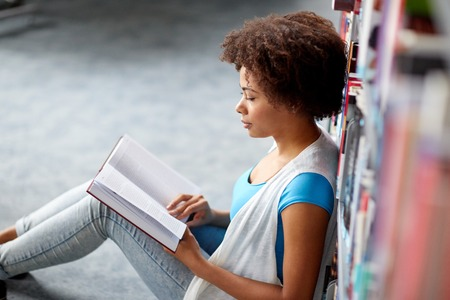 education, high school, university, learning and people concept - african american student girl reading book sitting on floor at library Stock Photo
