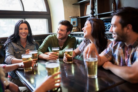 people, leisure, friendship and communication concept - happy friends drinking beer, talking and clinking glasses at bar or pub Stock fotó