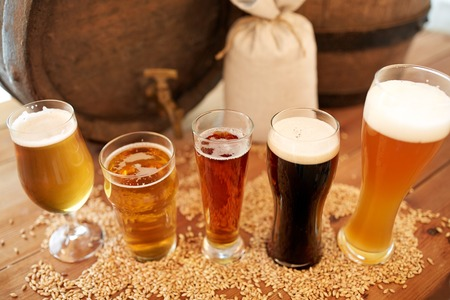 beerhouse: brewery, drinks and alcohol concept - close up of old beer barrel, glasses and bag with malt on wooden table Stock Photo