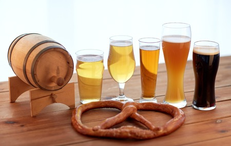 alehouse: brewery, drinks and food concept - close up of different beer glasses, wooden barrel and pretzel on table