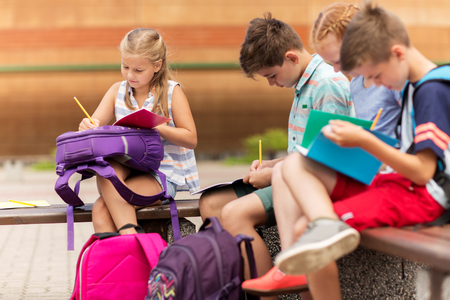 elementary schools: primary education, friendship, childhood, communication and people concept - group of happy elementary school students with backpacks and notebooks sitting on bench and doing homework outdoors