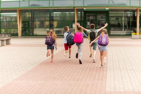 primair onderwijs, vriendschap, jeugd en mensen concept - groep van gelukkige basisschoolleerlingen met rugzakken buitenshuis draait Stockfoto