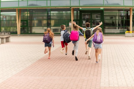 elementary: primary education, friendship, childhood and people concept - group of happy elementary school students with backpacks running outdoors Stock Photo