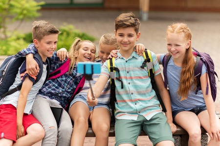 primary education, technology, friendship, childhood and people concept - group of elementary school students with backpacks sitting on bench and taking picture by smartphone on selfie stick outdoors Imagens