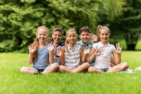 friendship, childhood, leisure and people concept - group of happy kids or friends waving hands in summer park Stock Photo