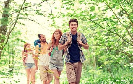 abenteuer, reise, tourismus, wandern und Personen-Konzept - Gruppe von lächelnden Freunden zu Fuß mit Rucksack in Holz Lizenzfreie Bilder - 64214508