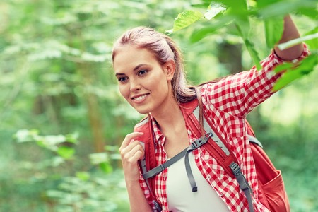 mochila de viaje: adventure, travel, tourism, hike and people concept - smiling young woman with backpack hiking in woods