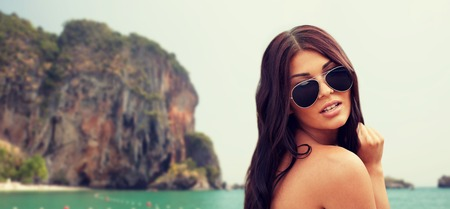 hispanic woman: summer vacation, tourism, travel, holidays and people concept -face of young woman with sunglasses over rock on bali beach background Stock Photo