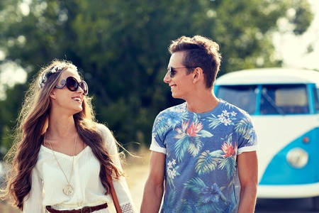 casual fashion: summer holidays, road trip, vacation, travel and people concept - smiling young hippie couple talking over minivan car