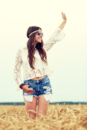 mujer hippie: nature, summer, youth culture, gesture and people concept - smiling young hippie woman in sunglasses on cereal field waving hand