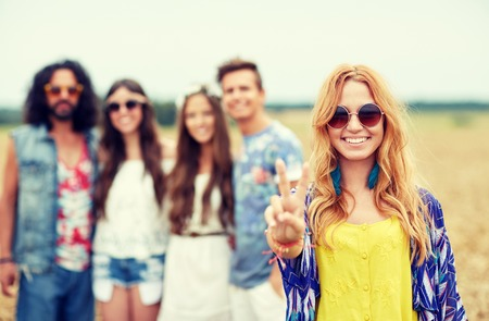 summer sign: nature, summer, youth culture, gesture and people concept - smiling young hippie friends in sunglasses showing peace hand sign on cereal field