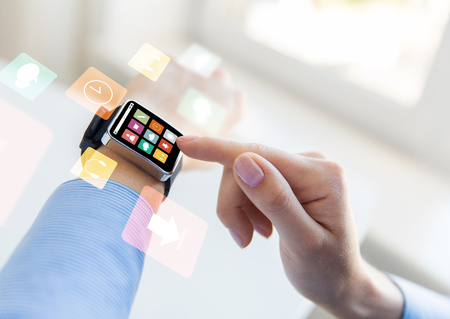 business, modern technology, media and people concept - close up of female hands setting smart watch with menu icons on screen at office