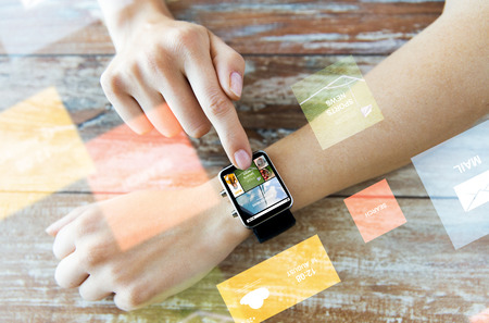 digital world: business, modern technology, media, internet and people concept - close up of female hands setting smart watch with news web page on screen on wooden table