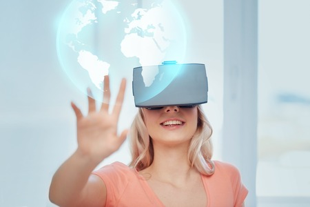 technology, augmented reality, entertainment and people concept - happy young woman with virtual headset or 3d glasses playing game at home looking at projection of earth globe