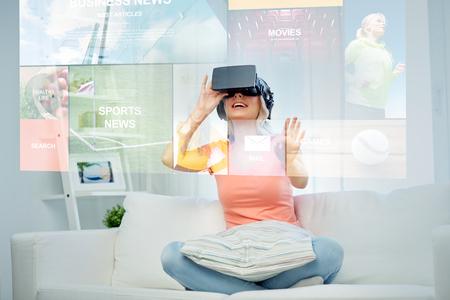 Technologie, Augmented Reality, Medien und Menschen Konzept - glückliche junge Frau, die in virtuellen Headset oder 3D-Brille und Kopfhörern auf Nachrichten Projektion zu Hause suchen Standard-Bild