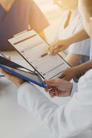 medical doctors: hospital, profession, people and medicine concept - close up of doctors with clipboard meeting and discussing medical report at medical office Stock Photo