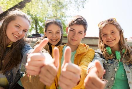vriendschap, gebaar en mensen concept - gelukkige tiener vrienden of middelbare scholieren zien thumbs up