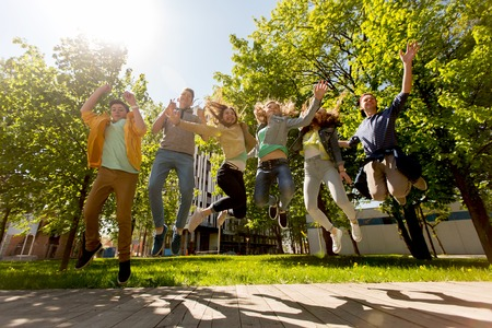 young group: friendship, motion, action, freedom and people concept - group of happy teenage students or friends jumping outdoors