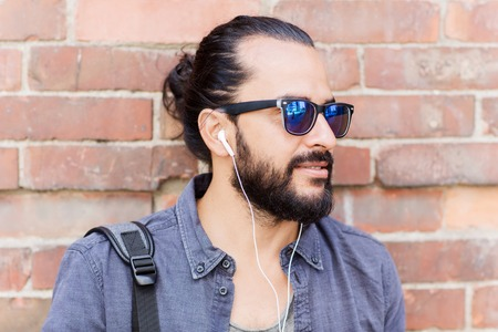 man style: people, music, technology, leisure and lifestyle - hipster man with earphones on city street listening to music