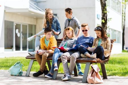 onderwijs, middelbare school en de mensen concept - groep van gelukkige tiener studenten met notebooks leren op de campus yard