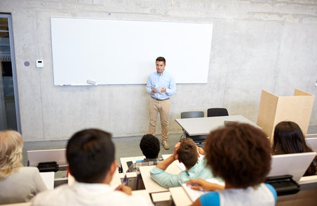 education, high school, university, teaching and people concept - group of international students and teacher with papers standing at white board at lecture